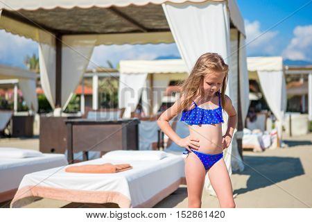 Cute little girl in swimsuit at beach during summer vacation