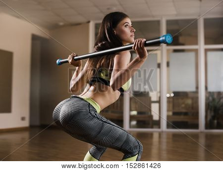 Back View Portrait Of A Young Woman Doing Squats With Barbell At Fitness Gym