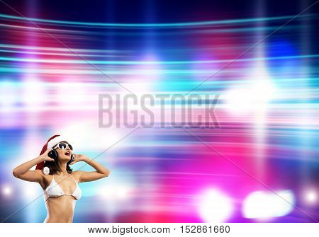 Beautiful young bikini girl in Santa Claus hat and headphones over bokeh background