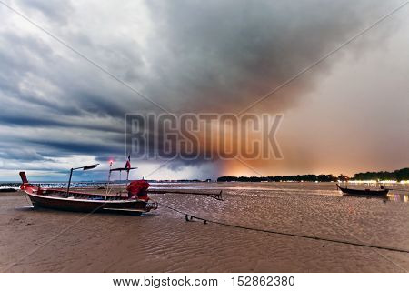 Sunset at tropical beach. Evening sea landscape with Thai traditional boat under dramatic stormy sky. Thailand