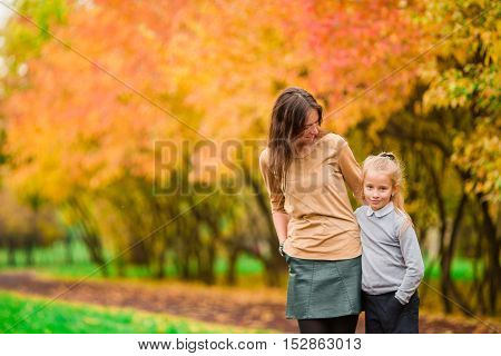 Young mother with cute little girl in autumn park on sunny day