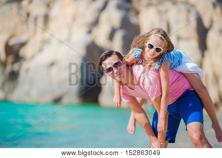 Happy father and his adorable little daughter enjoy summer vacation