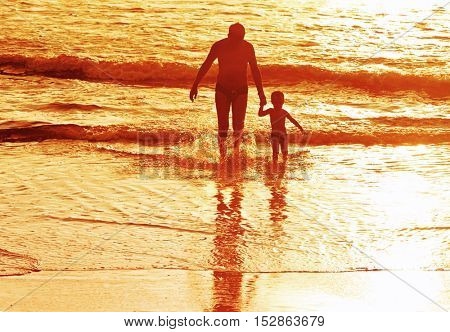 father with son at beach in the light of the setting sun