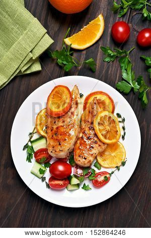 Roasted chicken breast with citrus orange sauce and vegetable salad on wooden background top view