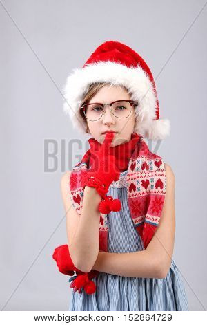 Christmas, X-mas, holidays, children, people concept - close-up portrait of surprised little girl in glasses and Santa helper hat over light background
