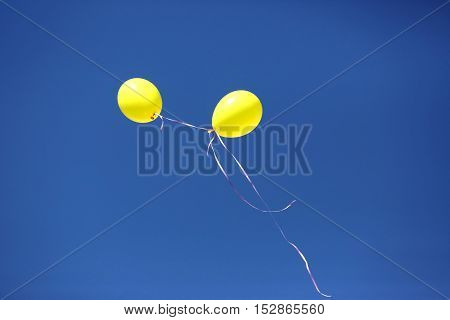 two yellow balloon against a blue sky