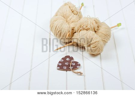 Natural woolen yarn with wood needles on the white wooden background.