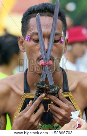 Phuket Town, THAILAND, October 06, 2016 : Devotee extreme piercing street procession during the Taoist vegetarian festival of the Nine Emperor Gods in Phuket, Thailand .