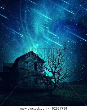 A ghost haunted house and a scary tree in the meadow below a cold dark blue sky. Spooky landscape with a starry night sky background and fallen comets.