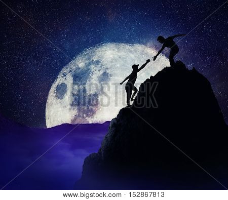 Man giving helping hand to friend to climb mountain rock cliff. Teamwork and trust concept in risky situation. Full moon night background.
