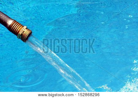 Close-up of garden hose water filling crystal blue water in swimming pool on bright hot summer day