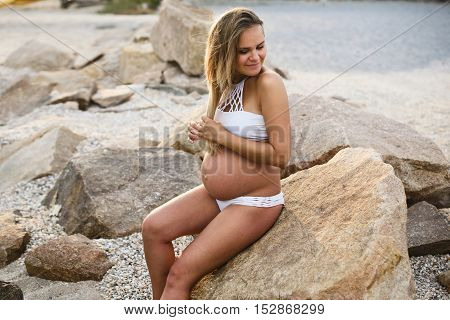 Young smiling  pregnant woman sitting at stones