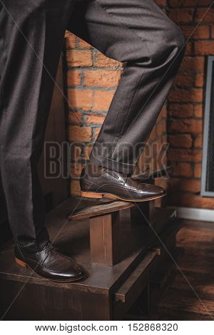 legs of a man standing on a wood retro stand station in waxed shoes