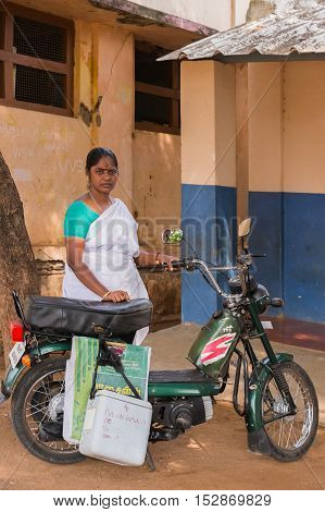 Dindigul India - October 22 2013: A public funded nurse swings by preschool to inoculate a kid with a polio shot. She wears white sari. Her fridge box hangs on motorcycle. School building background.