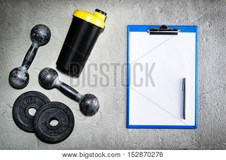 Fitness or bodybuilding concept background. Product photograph of old iron dumbbells on grey, conrete floor in the gym with blank page. Photograph taken from above, top view with lots of copy space