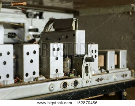 An open rear panel of a retro electronic device seems to be broken selective focus closeup. Technology background