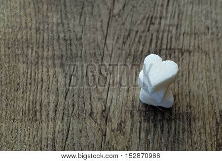 Three white sugar hearts on wooden table background
