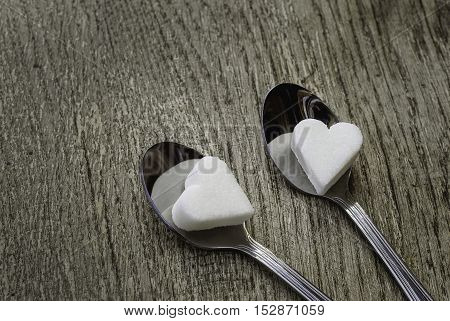 White sugar hearts with two tea spoons