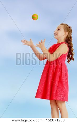 Beautiful Caucasian little girl in a bright orange dress, throws a little ball. On the pale blue background.