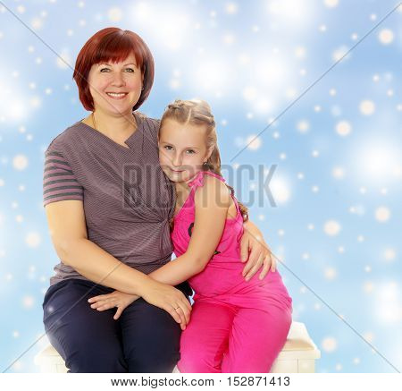 Happy family of two people, an adult mother, her beloved daughter 7 years cute cuddling on the couch. Blue Christmas festive background with white snowflakes.