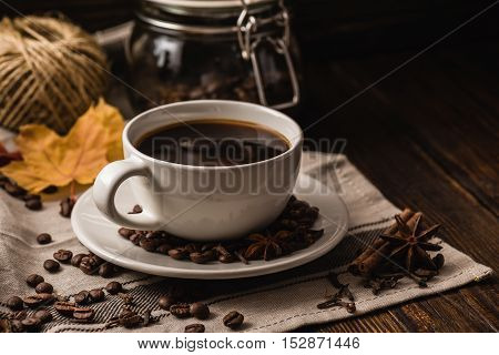 White cup of coffee with various spices beans and yellow autumn leaves on dark wooden background