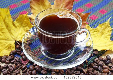 Coffee and yellow autumn leaves on a fabric background