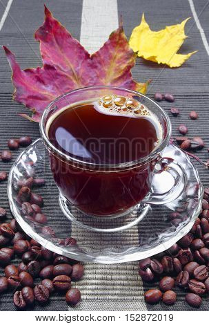 Cup of hot coffee and maple autumn leaves