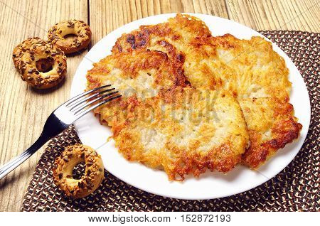 Potato pancakes on a plate on a wooden background