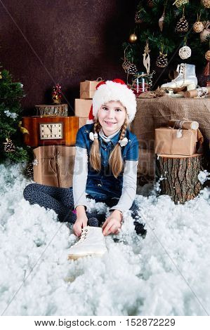 Little girl in Santa hat puts on the ice skates, Christmas tree and decorations background.