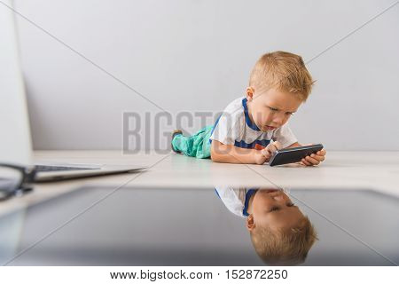 Having fun with my phone. Cropped shot of cute little boy lying on floor and using mobile phone against grey wall