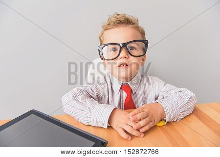 Learning through internet. Close up shot of small boy wearing glasses and sitting at desk with digital tablet next to him isolated on grey background