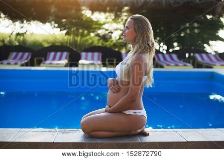Beautiful pregnant woman in swimming pool, summertime