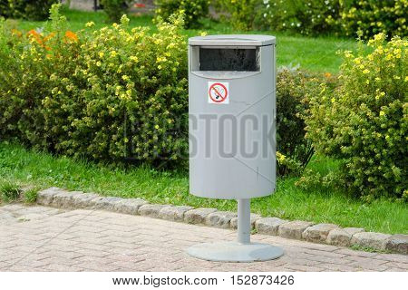 Accurate cylindrical metal rubbish bin on a background of a well-kept lawn