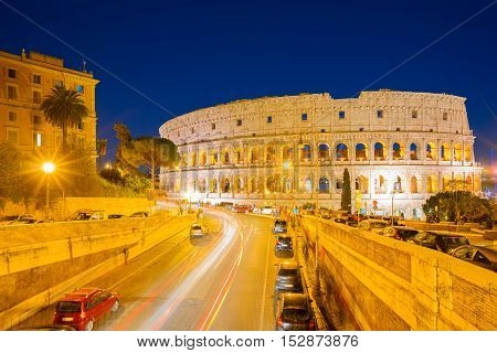 view of Colosseum illuminated at nighwith traffic lightst in Rome, Italy