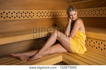 Beautiful caucasian woman with yellow towel relaxing in sauna