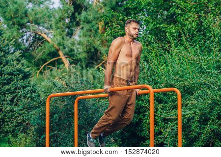 fitness, sport, exercising, training and lifestyle concept - young man doing triceps dip on parallel bars outdoors.