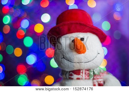Holiday Decorations, Christmas background. Snowman in red hat on lights background.
