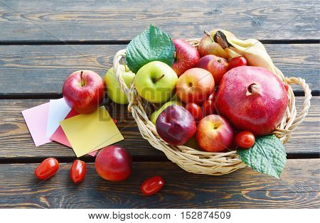 Colorful mixed fruits in the basket and paper for write a message on wooden old floor
