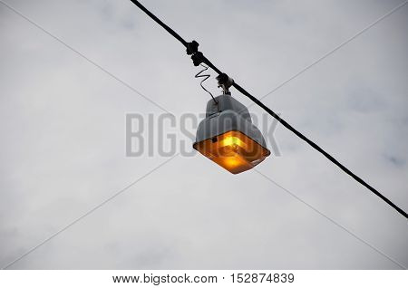 street lamp on wire with orange light outdoor on dark cloudy grey sky background