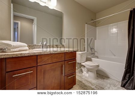 Clean And Warm Bathroom Interior With Tile Floor And Beige Walls