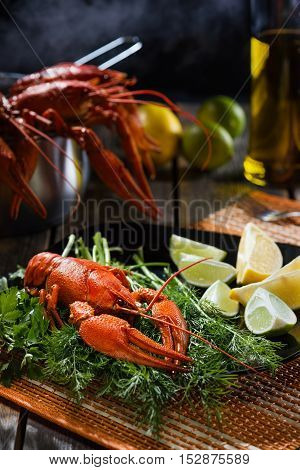Boiled crayfish with fresh greens and a citrus on a black ceramic plate in style a rustic