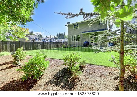 Backyard Area Of American Gray House With Well Kept Lawn