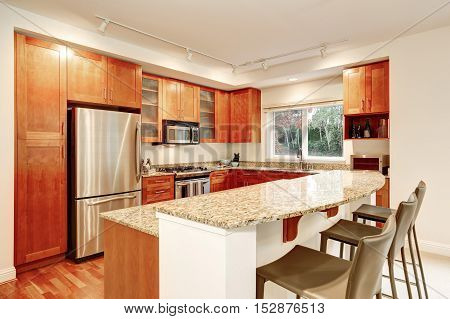 Kitchen Interior. Wooden Cabinets, Granite Tops And Window View