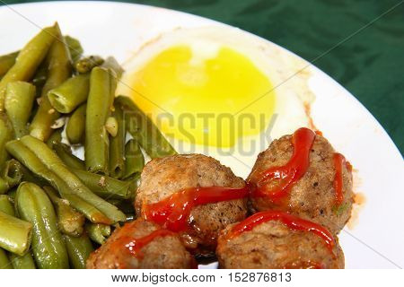 Swedish meatballs with green beans and scrambled eggs on table