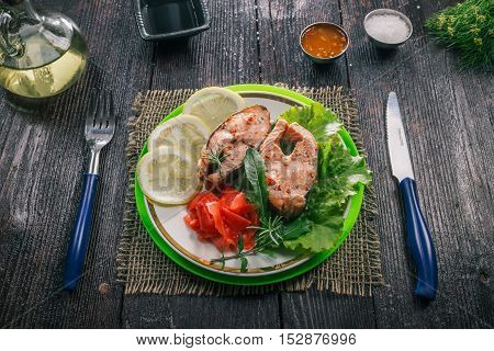 Cooked and garnished salmon steaks on the plate with condiments and vegetables on the background