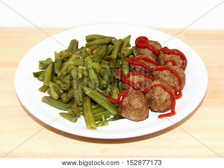 Swedish meatballs with green beans on wood