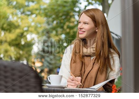 Pensive young woman is dreaming and writing into notebook with inspiration. She is sitting at table in cafe and smiling
