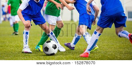 Soccer game for kids. Children kicking football ball
