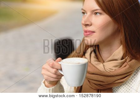 Relaxed girl is drinking coffee with pleasure in cafeteria. She is looking aside and dreaming
