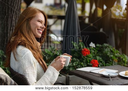 Happy young woman is drinking coffee in cafeteria outdoors. She is dreaming and smiling